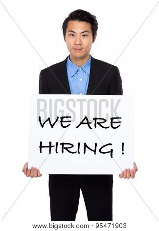 Confident businessman showing a placard showing with we are hiring phrases
