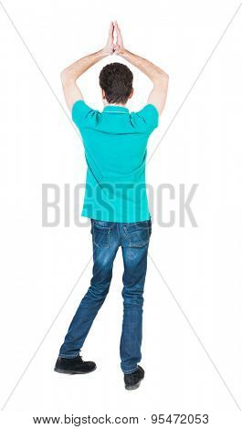 A man raised his hands in prayer.   Standing young man. Rear view people collection.  backside view of person.  Isolated over white background. The guy in a stylish aquamarine shirt praying.