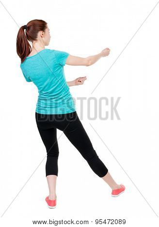 back view of standing woman pulling a rope from the top or cling to something.  Rear view people collection.  Sport girl in black tights standing in the pose of a man pulling a rope.