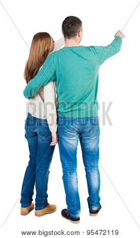 young couple pointing at wal Back view  (woman and man). Rear view people collection.  Isolated over white background. Man and woman embracing each other to point the finger somewhere to the right.