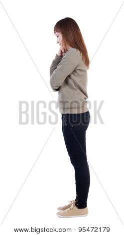 back view of standing young beautiful  woman.  girl  watching. Rear view people collection.   Isolated over white background. Girl standing sideways, wondering resting his fist on the cheek.