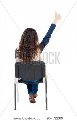 back view of young beautiful  woman sitting on chair and thumbs up. girl  watching. Rear view people collection.  Girl in sleeveless sheep sits on a chair and showing a thumbs up hand.