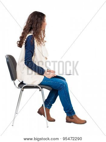 back view of young beautiful  woman sitting on chair.  girl  watching. Rear view people collection.   Isolated over white background. Girl in sleeveless sheep sits on a chair and holding a document.