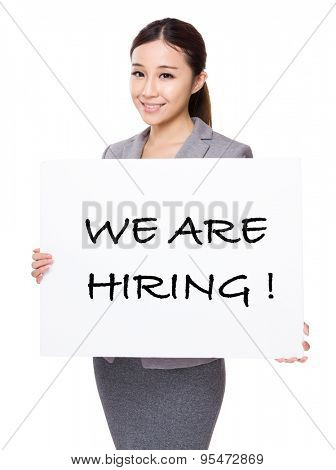 Businesswoman holding a board showing with we are hiring phrases