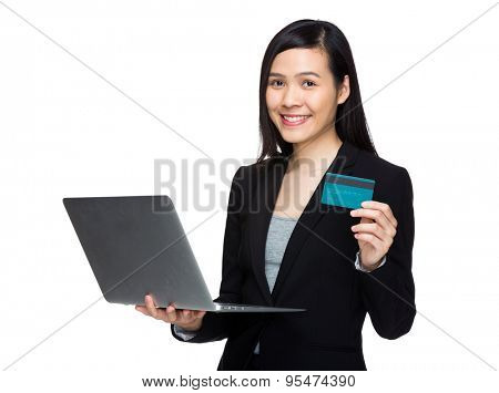 Businesswoman holding credit card and laptop computer for online payment concept