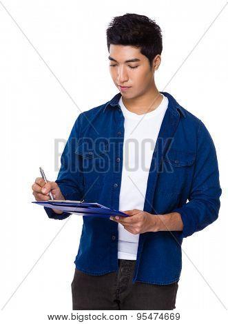 Man take note on clipboard