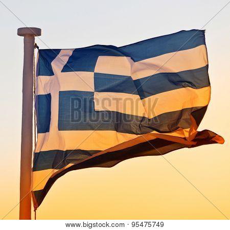 greek flag at sunset in santorini