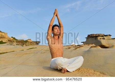 Young man doing yoga sitting in outdoors