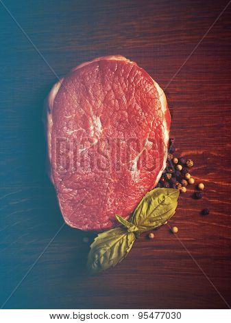 fresh raw steak with pepper and basil on the wooden board. Filtered image:cross processed vintage effect.