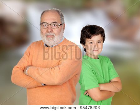 Two generations, grandfather and grandson with crossed arms and unfocused background