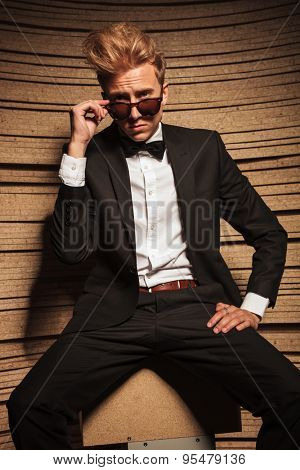 Elegant blond business man sitting while taking off his sunglasses.