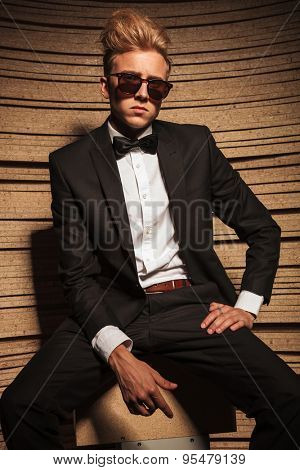 Portrait of a young elegant business man wearing suglasses, sitting on a chair.