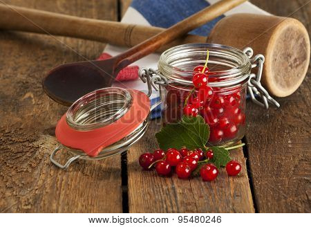 Redcurrant in jam glass and on rustic table with kitchen utensils