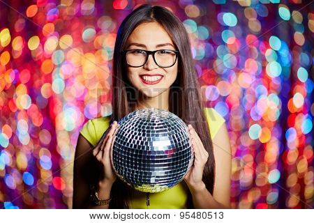 Posh girl with disco ball looking at camera in club