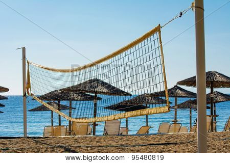 Volleyball net on the beach with umbrellas and chairs in the background