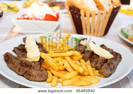 Grilled kebab - barbecued minced meat with french fries served on a table