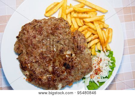 Burger with french fries served on a table - top view
