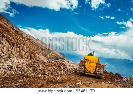 Bulldozer doing road constractuion on Kardung La pass in Himalayas. Ladakh, Jammu and Kashmir, India