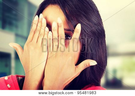 Shy woman peeking through covered face