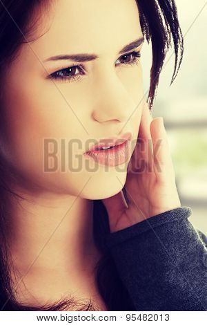 Teen woman pressing her cheek with painful expression