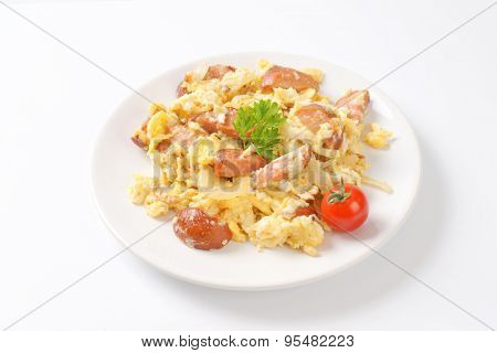 plate of scrambled eggs with onion and sliced sausage on white background