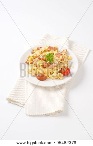 plate of scrambled eggs with onion and sliced sausage on white place mat