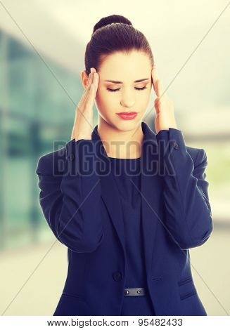 Young businesswoman suffering a headache