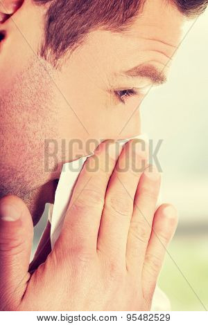 Sick young man blowing his nose