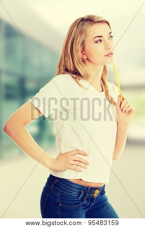 Thoughtful woman with pencil in her hand