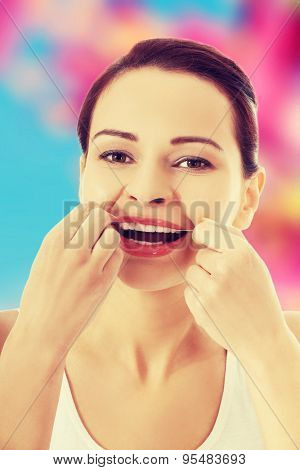 Beautiful woman flossing her teeth