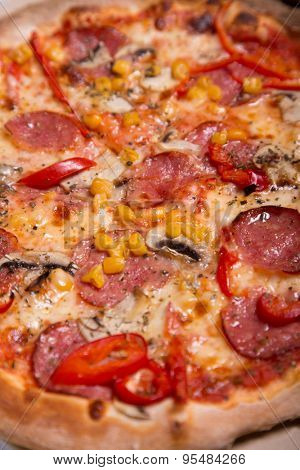 Tasty Italian pizza with pepperoni, corn and mushrooms, selective focus