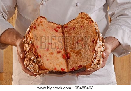 Baker holding panettone bread. Half panettone bread.