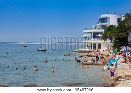 SELCE, CROATIA - JULY 04, 2015: People enjoying in swimming and sunbathing on the beach. Just a few steps from the Adriatic Sea, the modern-style Luxury Hotel Amabilis has a private beach.
