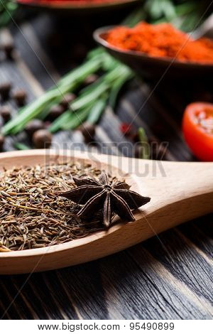 Spices. Spices in wooden spoon over wooden background. Zira and star anise