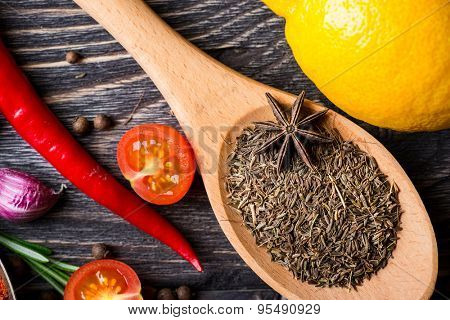 Spices. Spices in wooden spoon over wooden background. Zira and star anise, lemon and pepper.