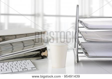 Closeup of a business desk with in-box-, binders, keyboard and disposable coffee cup in front of a large modern office window. The window is out of focus and high key. All items are white or silver.