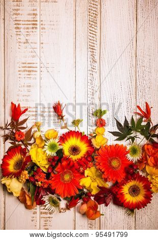 Autumnal flowers and berries on vintage wooden background. Top view with copy space