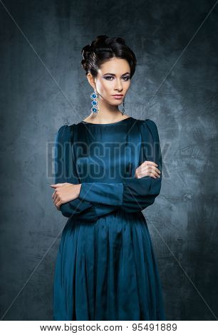 Young and beautiful fashion model posing posing in a teal dress