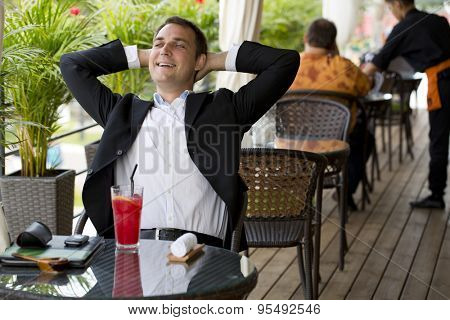 Portrait of a young happy business man in a dark suit and white shirt sitting in summer cafe