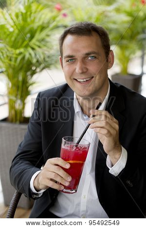 Portrait of a young business man in a dark suit and white shirt sitting in summer cafe