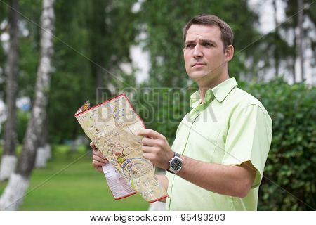 Young male tourist with map in hand looking around. Tourist map of the city of Moscow, Russia (no trademark)