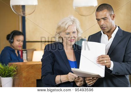 Businesspeople discussing over documents in front of reception desk at office