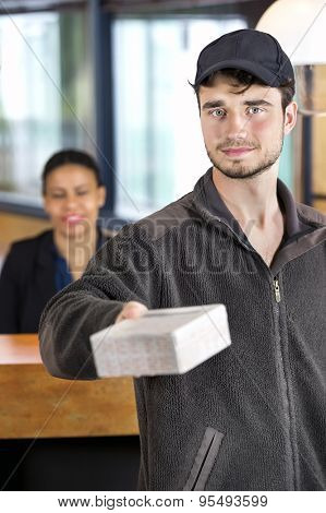Portrait of confident delivery man giving package while standing at reception desk in office