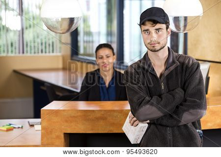 Portrait of delivery man holding package while standing at reception counter in office