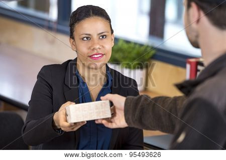 Happy female receptionist receiving parcel from delivery man in office