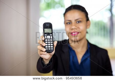 Portrait of smiling female receptionist holding cordless phone in office