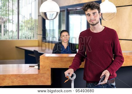 Portrait of man with luggage and passport standing at hotel reception desk