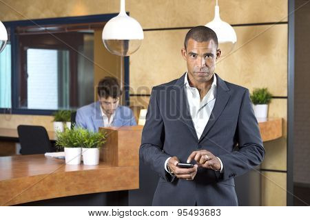 Portrait of confident businesswoman holding cellphone while receptionist working at desk in office