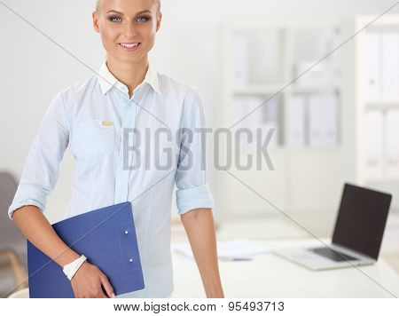 Attractive young businesswoman standing near desk with folder in the office.