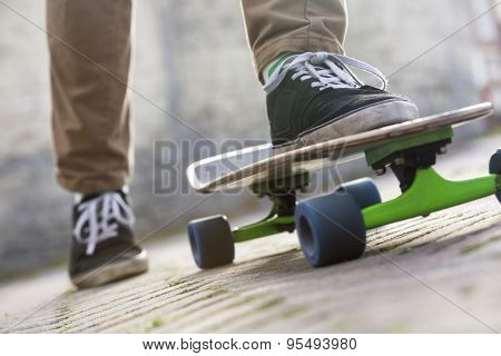 Cropped image of man skateboarding on footpath